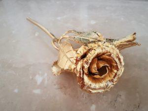 Rosa in ferro battutto poi dorata con oro zecchino appoggiata su marmo